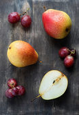 Fresh red pears and grapes on the dark wooden table — Stock Photo