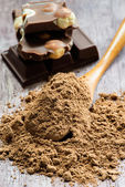 Cocoa powder and chocolate on a wooden board — Stock Photo