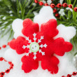 Snowflake toy Christmas decoration over decorated tree — Stock Photo