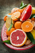 Fresh citrus fruits on rustic background — Stock Photo