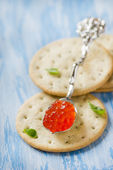 Red caviar in spoon on crackers — Stock Photo