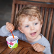 Adorable baby boy with blond hairs and blue eyes eating ice cream — Stock Photo