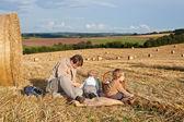 Pai jovem e seus rapazes da criança fazendo piquenique no campo dourado — Fotografia Stock