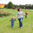 Young mother and her son running through field with lily bouquet — Stock Photo