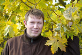 молодой человек с желтые кленовые листья осень — Стоковое фото