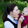 Young woman and adorable baby boy playing with lollipop summer — Stock Photo
