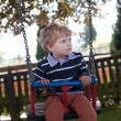 Cute toddler on playground swing summer — Stock Photo