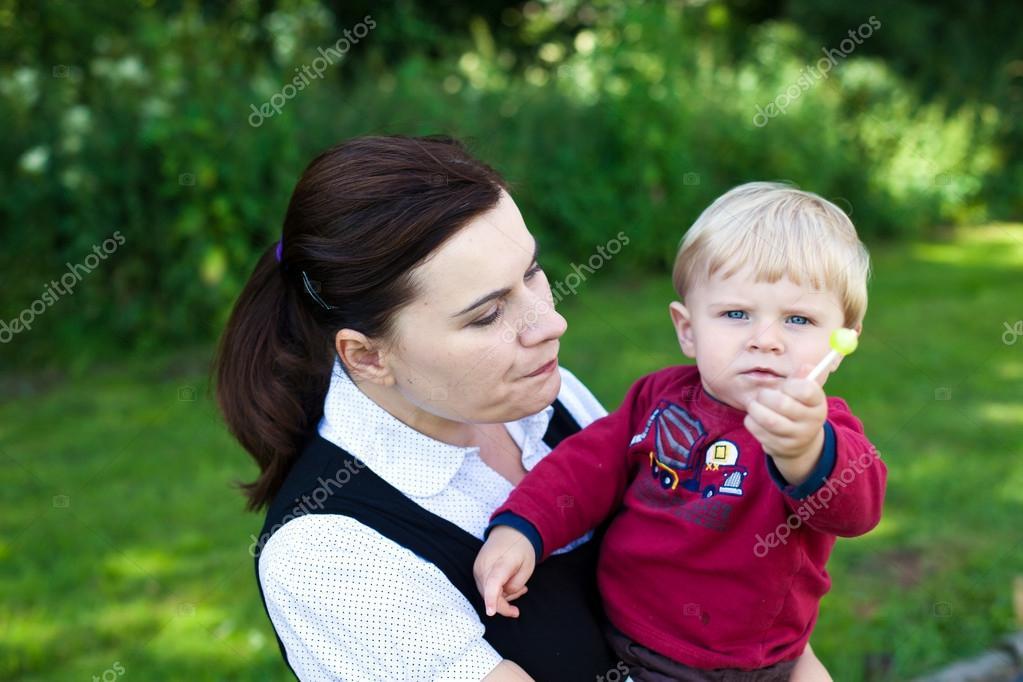 年轻的母亲和棒棒糖夏天玩可爱蹒跚学步