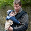 Young father and his son in rucksack in autumn park — Stock Photo