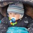 Little baby boy in pram in winter clothes with snowfall — Stock Photo