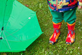 Green rain umbrella and children autumn boots — Stock Photo