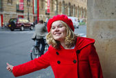 Beautiful young woman in red coat waiting taxi — Stock Photo