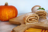 Swiss roll biscuit with pumpkin and apricot filing on wooden cut — Stock Photo