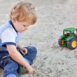 Little toddler boy playing with sand and toy — Stock Photo