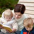 Young mother and toddler reading book outdoor — Stock Photo