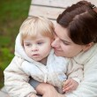 Young mother and toddler on bench in park — Stock Photo