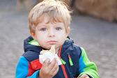 Adorable toddler eating bread outdoor — Stock Photo