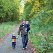 Stock Photo: Young father and his toddler boys walking in autumn forest