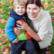 Little toddler boy and young mother in the autumn park — Stock Photo #13776255