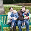 Family of four at beautiful autumn day on bench — Stock Photo
