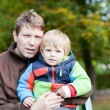 Young father and toddler boy in autumn park — Stock Photo