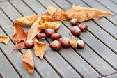 Chestnuts with leaves on wooden table — Stock Photo