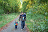 Young father and his toddler boys walking in autumn forest — Stock Photo