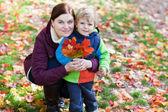 Sonbahar parkta güzel yürümeye başlayan çocuk ve genç kadın — Stok fotoğraf