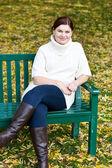 Sonbahar parkta bankta oturan güzel kadın — Stok fotoğraf
