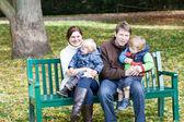 在美丽的秋天天在长凳上的四人家庭 — 图库照片