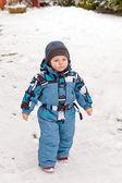 Kışın kar ile oynarken küçük yürümeye başlayan çocuk — Stok fotoğraf