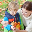 Little toddler boy and young mother in the autumn park — Stock Photo #13867799