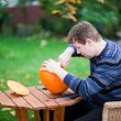 Young man making halloween pumpkin — Stock Photo