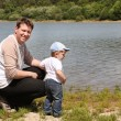 Young man with toddler boy on lake in summer — Stock Photo #14047085
