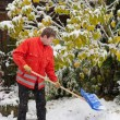 Adult man clean owns road to home against snow — Stock Photo #14047457