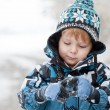Adorable toddler boy having fun with snow on winter day — Stockfoto