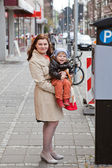 Young mother and toddler boy on city street — ストック写真