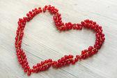 Hart gemaakt met rode bessen bessen op houten tafel — Stockfoto