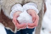 Manos de mujer con corazón de nieve — Foto de Stock