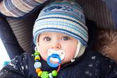 Baby boy in pram during winter snow fall — Stock Photo