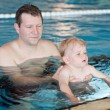 Father and baby boy swimming in a swimming pool — Stock Photo #14297509