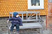 蹒跚学步的小男孩,坐在长凳上 — 图库照片
