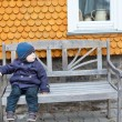 Little toddler boy sitting on bench — Stock Photo