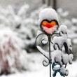 Red iron heart with snow outdoors - Foto Stock