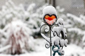 Red iron heart with snow outdoors — Stock Photo
