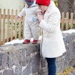 Mother and toddler boy having fun with snow on winter day — Stock Photo