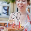 Birthday cake with candles and 30 with woman on background — Stock Photo