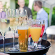 Waiter with dish of champagne, coctails, beer and juice glasses - Foto Stock