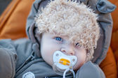 Adorable baby boy in winter clothes sleeping in stroller — Stock Photo