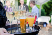 Waiter with dish of champagne, coctails, beer and juice glasses — Stock Photo